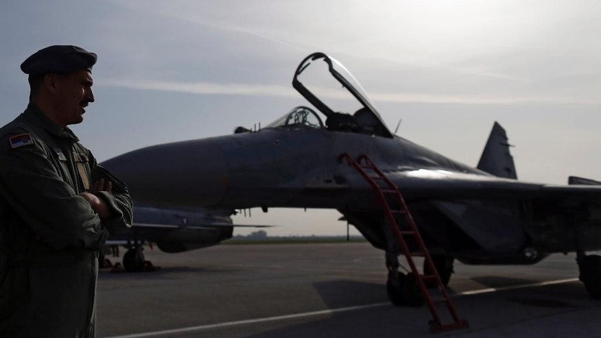 In this photo taken Wednesday, April 6, 2016, a pilot stands by a MiG 29 fighter jet at the Batajnica military airport outside Belgrade, Serbia. Serbia's defense minister Zoran Djordjevic said Sunday, March 12, 2017, that the country is expecting Russian President Vladimir Putin's approval for the delivery of fighter jets, which could worsen tensions with neighboring states. (AP Photo/Darko Vojinovic)