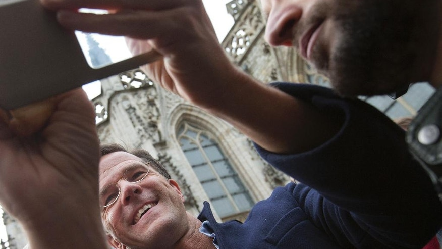 Dutch Prime Minister Mark Rutte takes a selfie with a well-wisher during a campaign stop in Breda, Netherlands, Saturday, March 11, 2017. (AP Photo/Peter Dejong)