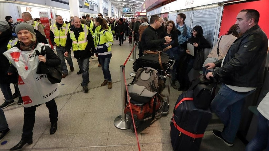 Participants of a strike organized by the German ver.di union walk past travelers queuing in front of a booking change counter at the Tegel airport in Berlin, Germany, Monday, March 13, 2017. The union, representing airport ground staff, has called on its members to go on strike again at Berlin's two airports Tegel and Schoenefeld. (AP Photo/Michael Sohn)