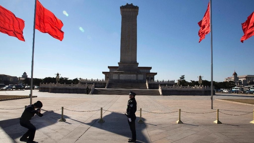 In this Sunday, March 12, 2017 photo, a Chinese police officer stands in front of the Monument to the People's Heroes on Tiananmen Square in Beijing, China. Damaging the reputation and honor of heroes and martyrs could be a civil offense under a proposed draft of China's civil law as the Communist Party further tightens the space for public discourse on historical issues. (AP Photo/Ng Han Guan)