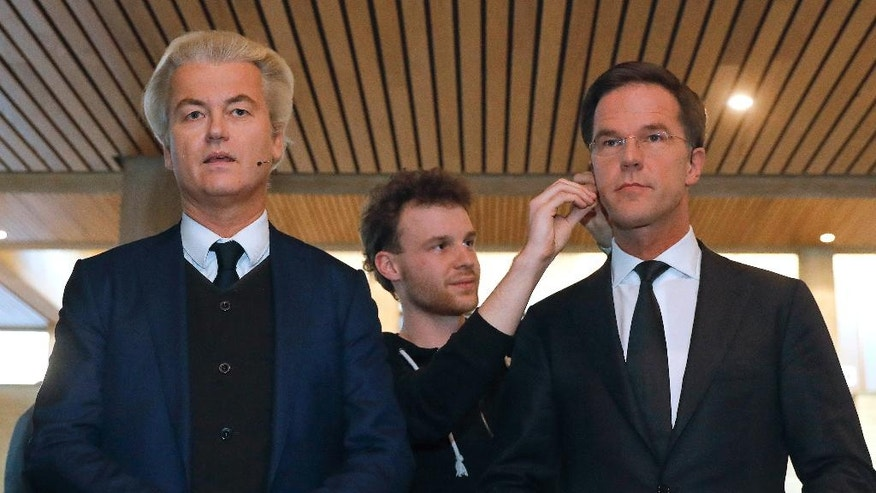 Dutch Prime Minister Mark Rutte, right, and right-wing populist leader Geert Wilders, get their microphones installed prior to a national televised debate, the first head-to-head meeting of the two political party leaders since the start of the election campaign, at Erasmus University in Rotterdam, Netherlands, Monday, March 13, 2017. (Yves Herman POOL via AP)