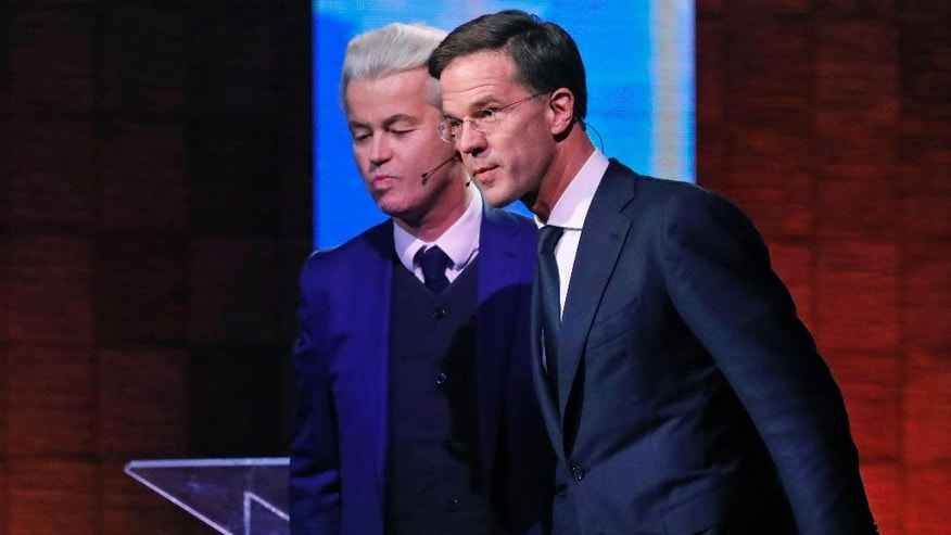 Dutch Prime Minister Mark Rutte, right, and Right-wing populist leader Geert Wilders leave after a national televised debate, the first head-to-head meeting of the two political party leaders since the start of the election campaign, at Erasmus University in Rotterdam, Netherlands, Monday, March 13, 2017. (Yves Herman POOL via AP)