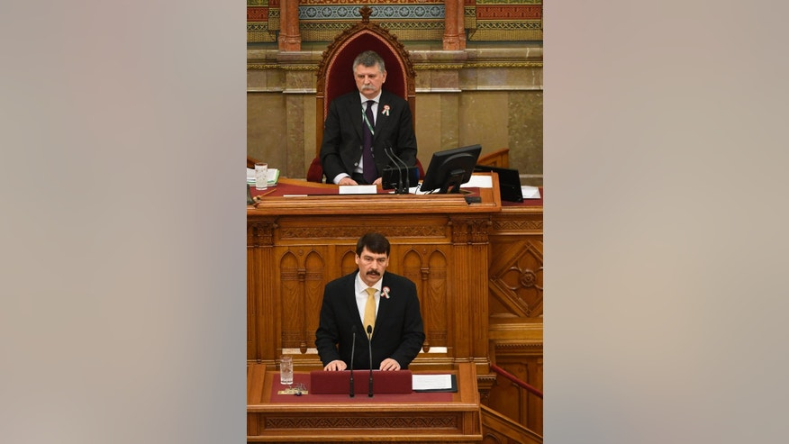 Hungarian President Janos Ader delivers his speech in the foreground of Speaker of the Parliament Laszlo Kover during the plenary session of the unicameral Hungarian Parliament in Budapest, Hungary, Monday, March 13, 2017, when the deputies elect the President of Hungary for the next term of five years. Janos Ader is up against the candidate of the opposition coalition Laszlo Majtenyi for the post. (Szilard Koszticsak/MTI via AP)
