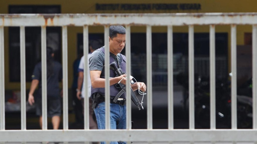 "A police officer carries machine gun patrol inside forensic department at Kuala Lumpur Hospital in Kuala Lumpur, Malaysia on Sunday, March 12, 2017.  Malaysia's Foreign Minister Anifah Aman said the government hopes to begin formal talks with North Korea in the ""next few days"" on solving a diplomatic dispute that has seen the two countries bar each other's citizens from leaving. The dispute stems from the mysterious poisoning death of the estranged half brother of North Korean leader Kim Jong Un on Feb. 13 at Kuala Lumpur's airport. (AP Photo/Daniel Chan)"