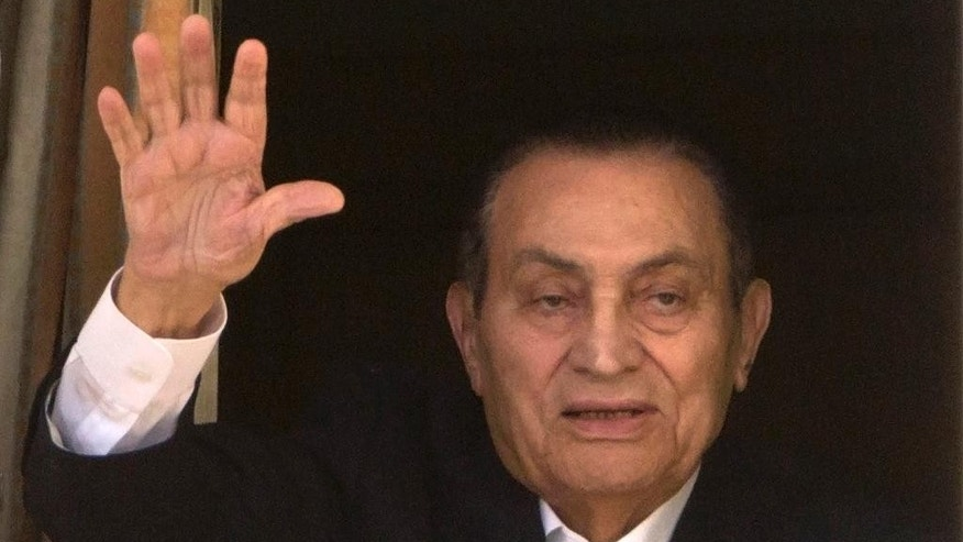 FILE - In this April 25, 2016 file photo, ousted Egyptian President Hosni Mubarak waves to his supporters from his room at the Maadi Military Hospital, where he is hospitalized, as they celebrate Sinai Liberation Day that marks the final withdrawal of all Israeli military forces from Egypt's Sinai Peninsula in 1982, in Cairo, Egypt. Egypt's state news agency says prosecutor has ordered the release of ousted President Hosni Mubarak on Monday, March 13, 2017. (AP Photo/Amr Nabil, File)