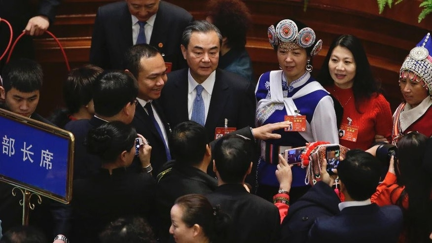 In this Sunday, March 12, 2017 photo, Chinese Foreign Minister Wang Yi, center, is surrounded by delegates for souvenir photographs before a plenary session of the National People's Congress held at the Great Hall of the People in Beijing. Talks between China and the 10 members of the Association of Southeast Asian Nations has produced a draft version of a long-awaited code of conduct aiming to reduce the potential for conflicts in the South China Sea, Wang told reporters on Wednesday, March 8. (AP Photo/Andy Wong)