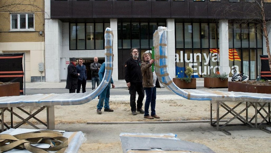 Belgian artist Jean-Henri Compere, center left, overseas the installation of his his new sculpture in the EU quarter of Brussels on Monday, March 13, 2017. The sculpture, commemorates the Brussels attacks of March 22, 2016, as well as other European attacks. Titled 'Wounded but still standing in front of the inconceivable', it will be unveiled during a ceremony on March 22, 2017. (AP Photo/Virginia Mayo)