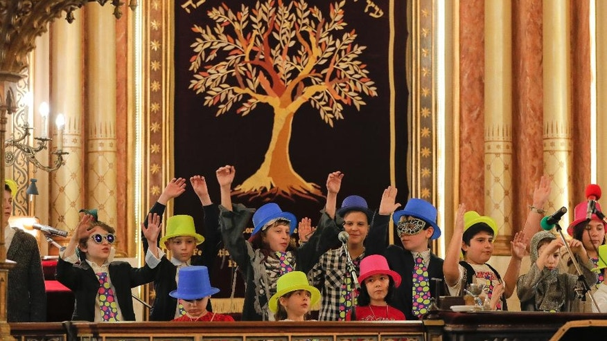 In this March 11, 2017 picture, children sing during Purim celebrations at the Coral Temple synagogue in Bucharest, Romania. Children put on fancy costume dress joining dozens of believers from Romania's Jewish community who attended a Purim service to celebrate the Jews' salvation from genocide in ancient Persia, as recounted in the Book of Esther.(AP Photo/Vadim Ghirda)