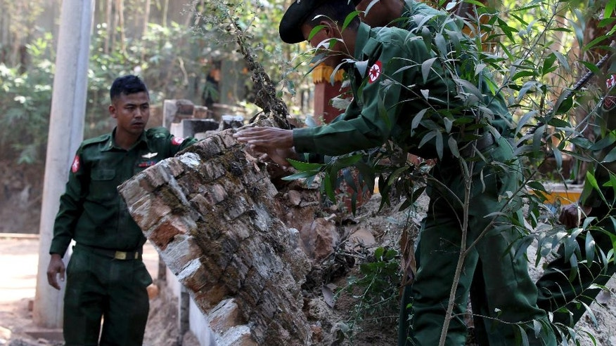 Myanmar soldiers remove debris from a fallen wall of a monastery hit by an earthquake in Taikkyi township northeast of Yangon, Myanmar, Tuesday, March. 14, 2017. The U.S. Geological Survey said the late Monday quake measured magnitude 5.1 and was centered about 70 kilometers (44 miles) northwest of Yangon at a relatively shallow depth of 10 kilometers (6 miles). Shallow earthquakes tend to cause more damage. (AP Photo/Thein Zaw)