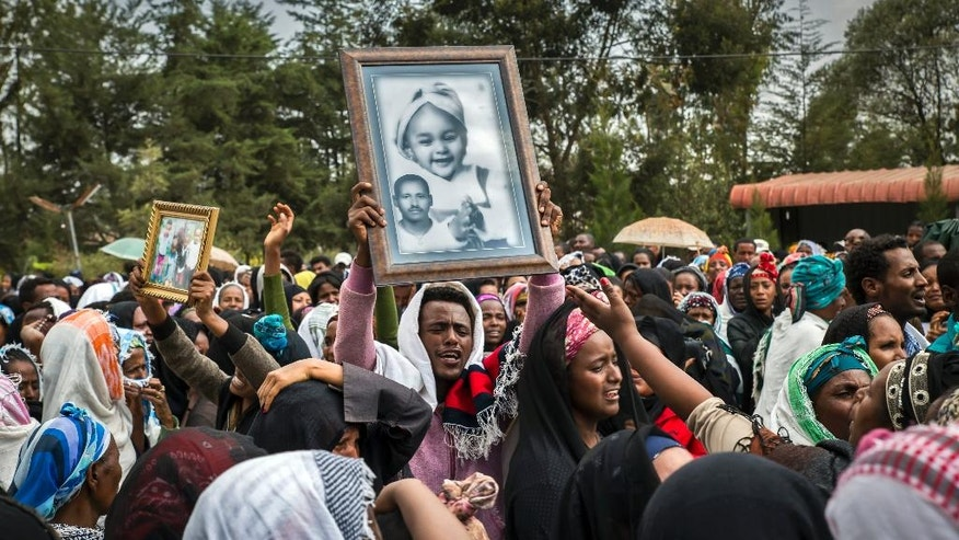 Relatives mourn as they lift portraits of family members they lost in the collapse of a mountain of trash at a garbage dump, during a funeral service held at the Gebrekristos church in Addis Ababa, Ethiopia, Monday, March 13, 2017. The death toll reached more than 60 on Monday from the collapse at the dump on the outskirts of the capital, according to the state-affiliated Fana Broadcasting Corporate, as relatives waited for news of the dozens of people said to be missing. (AP Photo/Mulugeta Ayene)