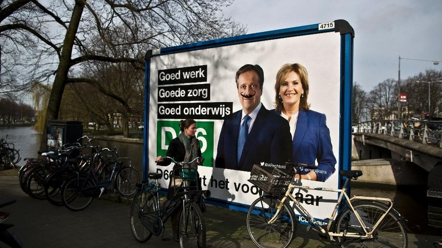 A woman pushes her bicycle past an election billboard with defaced images of Alexander Pechtold and Pia Dijkstra from Democrats 66 party, D66, in Amsterdam, Netherlands, Tuesday, March 14, 2017. Amid unprecedented international attention, the Dutch go to the polls Wednesday in a parliamentary election that is seen as a bellwether for the future of populism in a year of crucial votes in Europe. (AP Photo/Muhammed Muheisen)