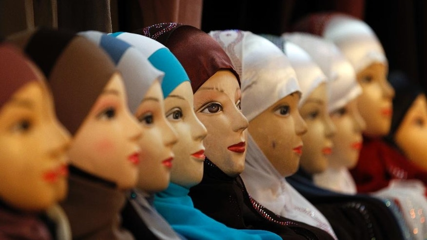 FILE - In this Dec.17, 2011 file photo, mannequins with headscarves are on display at an exhibition hall for the Muslim World Fair in Le Bourget, outside Paris. Private businesses in Europe can forbid Muslim women in their employ from wearing headscarves if the ban is part of a policy of neutrality within the company and not a sign of prejudice against a particular religion, the European Court of Justice said Tuesday March 14, 2017. (AP Photo/Christophe Ena, File)