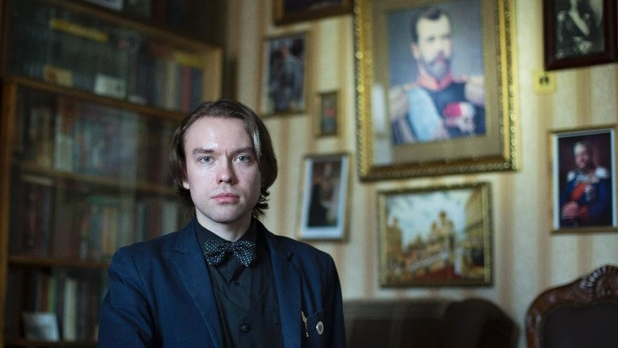 "In this photo taken on Wednesday, March 8, 2017, Pavel Isakov-Kundius, head of cultural programs at the Museum of the Imperial Family, poses for a photo in Moscow, Russia, with the portrait of Emperor Nicholas II in the background. For Isakov-Kundius, 24, monarchy or ""the worshiping of the ruler"" as he describes, is a trait that formed the Russian psyche. (AP Photo/Alexander Zemlianichenko)"