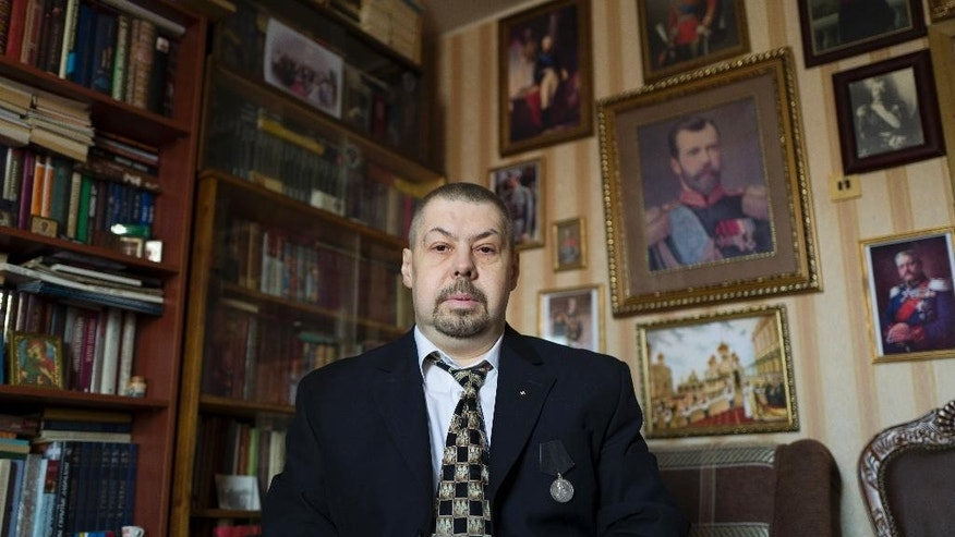 "In this photo taken on Wednesday, March 8, 2017, Alexander Fomin, deputy chairman of the All-Russian Monarchist Center, poses for a photo in Moscow, Russia, with the portrait of Emperor Nicholas II in the background. Fomin, 47, says the monarchs in Russia were ""guarantors of stability"" and ""the Anointed of the Lord"". (AP Photo/Alexander Zemlianichenko)"