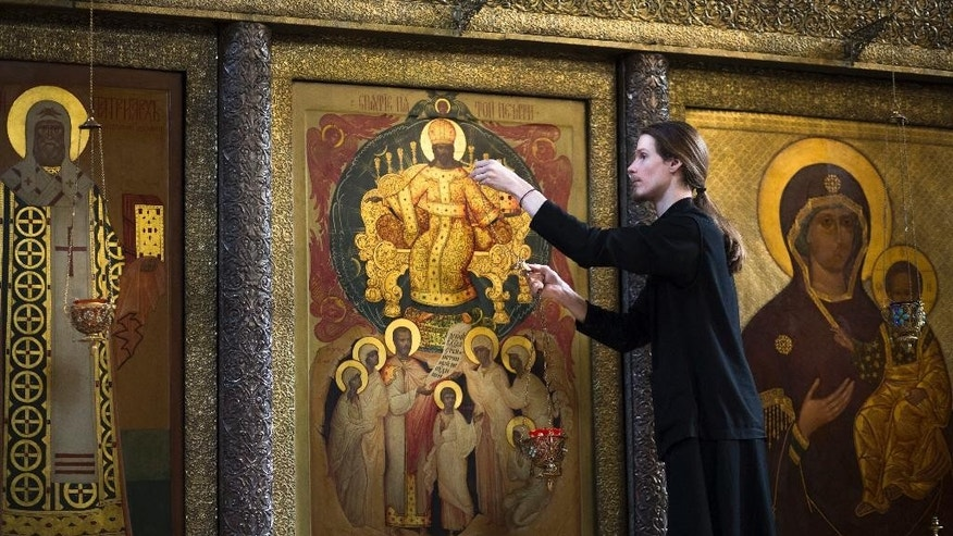 In this photo taken on Monday, March 13, 2017, an Orthodox priest hangs an icon-lamp in front of an icon depicting the family of Russia's Emperor Nicholas II and his family who were canonized as saints, at the Sretensky Monastery in Moscow, Russia . Russia's czarist era, which ended a century ago, was marked by cruelty and oppression, and finished in a chaotic spasm of blood, anger and confusion. But there are those in the country today who believe the monarchist system should be restored. (AP Photo/Alexander Zemlianichenko)