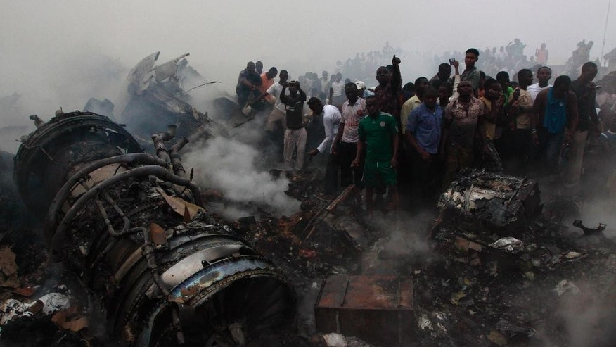 FILE- In this Sundy June. 3, 2012 file photo, people gather at the site of a plane crash in Lagos, Nigeria. An investigation into a June 2012 plane crash in Nigeria that killed some 153 people onboard and others on the ground has faulted the aircraft's pilot and raised long-standing questions over aviation safety in Africa's most populous nation. (AP Photo/Sunday Alamba File)