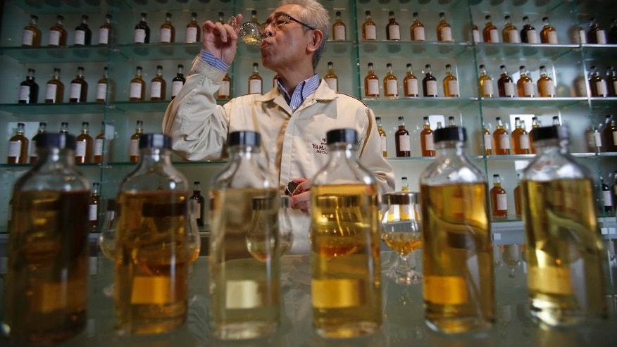 "In this March 8, 2017 photo, Suntory's chief blender Shinji Fukuyo demonstrates how he examines the whisky at the Suntory distillery in Yamazaki, near Kyoto, western Japan. ""What's important for whisky is that its deliciousness must deepen with aging, sitting in the casks for a long time,"" said Fukuyo, 55, demonstrating how he examines the whisky in a glass, swirling the crystalline amber spirit against the light. (AP Photo/Koji Ueda)"