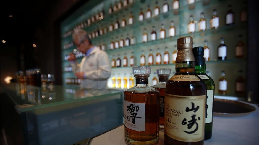 "In this March 8, 2017 photo, Suntory's chief blender Shinji Fukuyo demonstrates how he examines the whisky at the Suntory distillery in Yamazaki near Kyoto, western Japan with bottles of Hibiki, left, and Yamazaki 12 years single malt whisky are displayed on the counter. ""What's important for whisky is that its deliciousness must deepen with aging, sitting in the casks for a long time,"" said Fukuyo, 55, demonstrating how he examines the whisky in a glass, swirling the crystalline amber spirit against the light. (AP Photo/Koji Ueda)"