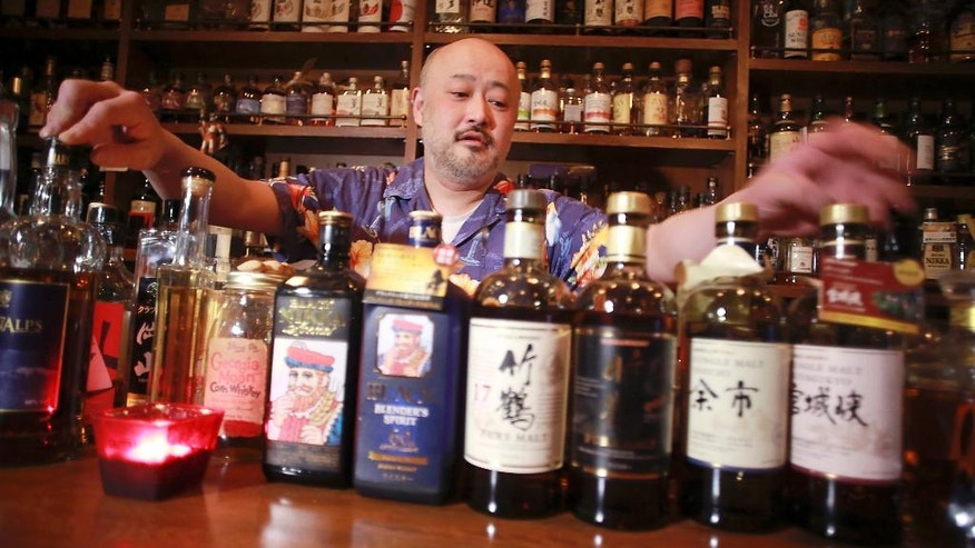 "In this March 10, 2017 photo, shot bar Zoetrope owner and bartender Atsushi Horigami adjusts the bottles of Japan-made whisky at his bar in Tokyo. Zoetrope, a tiny bar in a dingy building in a Tokyo backstreet, is famous among whisky lovers for specializing in Japanese whisky. ""Japanese whisky has an unpredictability that makes it fun, and the highly skillful Japanese blenders have created a subtle taste with an impeccable balance,"" said Horigami. (AP Photo/Eugene Hoshiko)"