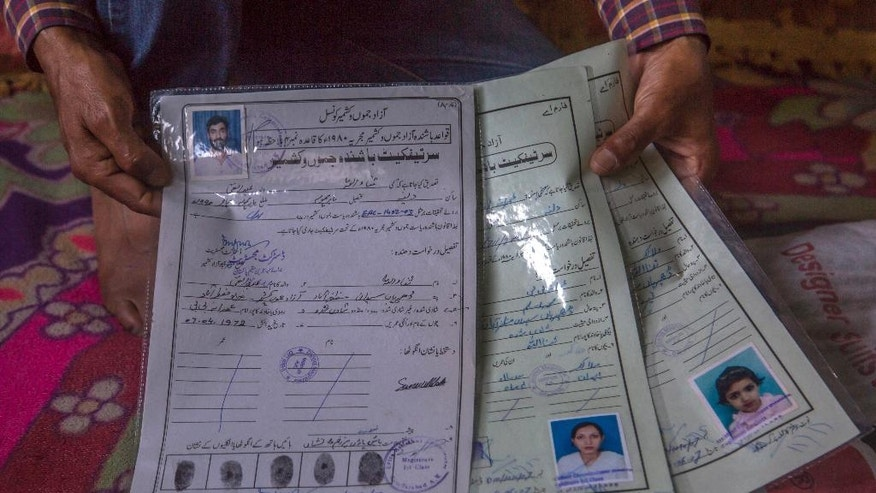 "In this June. 2, 2016, photo, Sonaullah Dar, a former Kashmiri militant, shows citizenship certificates of his family issued by authorities in Pakistan administered Kashmir at his residence in Delina, 50 kilometers (31 miles) north of Srinagar, Indian controlled Kashmir. ""We were lured to return to abject humiliation and deprivation,"" said the former fighter, now living in a single room with his Pakistani wife and two daughters since returning in 2013. Four years later, he is still spending his days running between government offices hoping to one day secure legitimate papers for India. (AP Photo/Dar Yasin)"