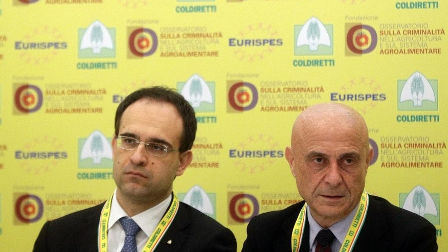 Italian Interior Minister Marco Minniti, right, and Coldiretti President Roberto Moncalvo present a report on organized crime infiltration in Italy's much prized food and agriculture businesses at the Coldiretti, the Italian farmers association headquarters in Rome, Tuesday, March 14, 2017. Organized crime has a seemingly insatiable appetite for farm and food businesses, one of the few economic sectors experiencing growth during Italy's protracted economic crisis. (AP Photo/Gregorio Borgia)