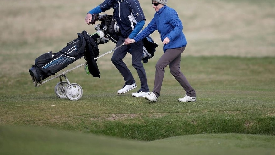 Woman golfer Jeanette Siehenthiler and her caddie walk to a green during a round of golf after it was announced that women will be admitted as members of Muirfield Golf Club after a membership ballot was held by The Honourable Company of Edinburgh Golfers, in Gullane, Scotland Tuesday, March 14, 2017. Muirfield Golf Club voted Tuesday to admit female members for the first time in its 273-year history, paving the way for the Scottish golf club to again host the British Open.  ( Jane Barlow/PA via AP)