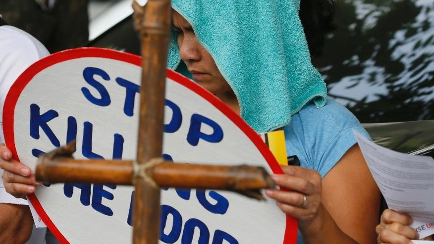 "A relative displays a ""Stop Killing The Poor"" message during a protest outside the Ombudsman building to lend support to Mary Ann D. Domingo, the widow and mother respectively of Luis Bonifacio and Gabriel Bonifacio as she files two counts of murder and administrative cases against Police Superintendent Ali Jose Duterte and at least seven other police officers in the killing last year of Luis and Gabriel Bonifacio inside their house, Tuesday, March 14, 2017 in suburban Quezon city, northeast of Manila, Philippines. The charges were one of a few cases filed against police officers by relatives since the so-called war on drugs by President Rodrigo Duterte killed more than 7,000 people in the first 8 months of his term. (AP Photo/Bullit Marquez)"
