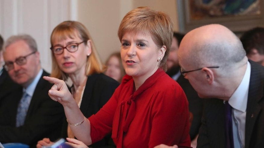 Scottish First Minister Nicola Sturgeon, center, gestures as she sits with Lord Advocate James Wolffe, left, Permanent Secretary Leslie Evans and Deputy First Minister John Swinney, right, during a Scottish Government cabinet meeting in Bute House, Edinburgh, Scotland Tuesday March 14, 2017.  Sturgeon announced on Monday plans for a fresh referendum on Scottish independence before Britain finally leaves the EU. (Jane Barlow/PA via AP)