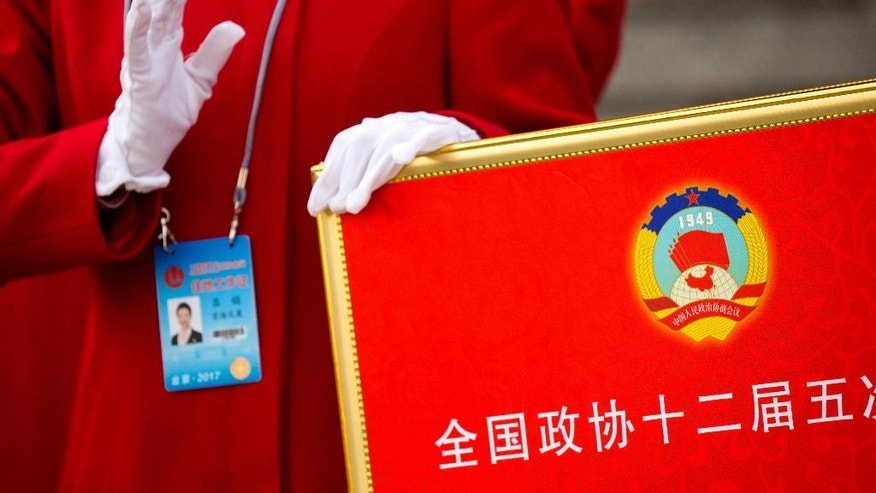 In this Friday, March 3, 2017 photo, a hospitality staff member holds a signboard with the logo of the Chinese People's Political Consultative Congress (CPPCC) as she directs delegates after the end of the opening session of the CPPCC at the Great Hall of the People in Beijing. The annual session of China's ceremonial legislature is designed to awe onlookers with its size and sweep, yet the experience is also made up of tiny moments, details that point to the personalities of the participants and the event's unique, sometimes quirky, traits that a casual observer might easily miss. (AP Photo/Mark Schiefelbein)