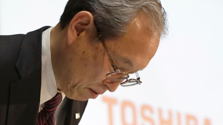 Toshiba Corp. President Satoshi Tsunakawa bows during a press conference at the company's headquarters in Tokyo, Tuesday, March 14, 2017. Troubled Japanese nuclear and electronics company Toshiba said Tuesday it was considering selling its money-losing Westinghouse operations in the U.S. (AP Photo/Eugene Hoshiko)