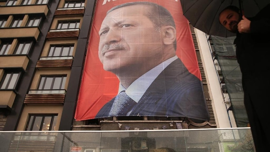 A poster with a picture of Turkish President Recep Tayyip Erdogan, is seen on a building, in central Istanbul's Taksim Square, Tuesday, March 14, 2017. Turkish President Recep Tayyip Erdogan on Tuesday directed fresh verbal attacks at the Netherlands amid their growing diplomatic spat, holding the country responsible for Europe's worst mass killing since World War II. In a televised speech, Erdogan referred to the massacre of some 8,000 Muslim men and boys in Srebrenica, eastern Bosnia, in 1995. (AP Photo/Lefteris Pitarakis)