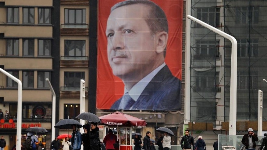 People walk in central Istanbul's Taksim Square, backdropped by a poster of Turkish President Recep Tayyip Erdogan, Tuesday, March 14, 2017. Turkish President Recep Tayyip Erdogan on Tuesday directed fresh verbal attacks at the Netherlands amid their growing diplomatic spat, holding the country responsible for Europe's worst mass killing since World War II. In a televised speech, Erdogan referred to the massacre of some 8,000 Muslim men and boys in Srebrenica, eastern Bosnia, in 1995. (AP Photo/Lefteris Pitarakis)