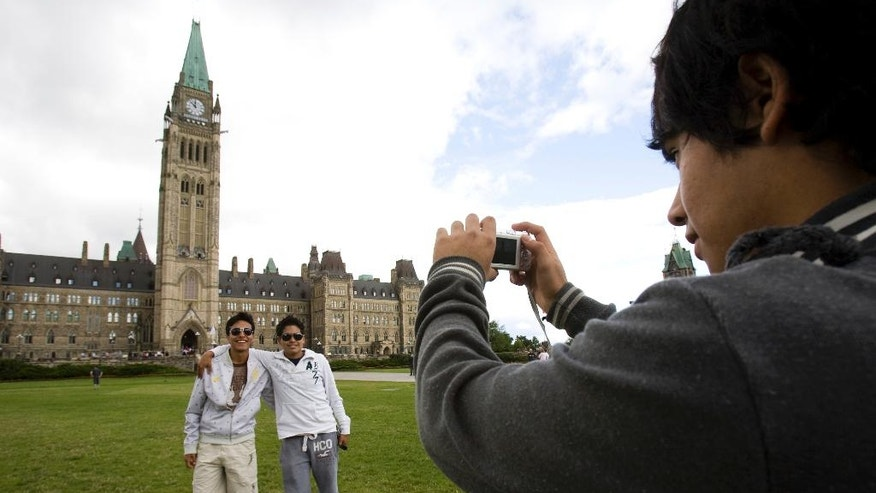 FILE - In this July 14, 2009, file photo, Mexican tourist Borris Frias takes a picture of his travel partners Noe Montano, left, and Erick Ruiz as they visit Parliament Hill in Ottawa, Canada. Canada has seen a surge of visitors from Mexico since December 2016, when it lifted a visa requirement that had been imposed in 2009. The change was planned before the U.S. election, but it is widely viewed as a reflection of warmer relations between Canada and Mexico. (AP Photo/The Canadian Press, Sean Kilpatrick, File)