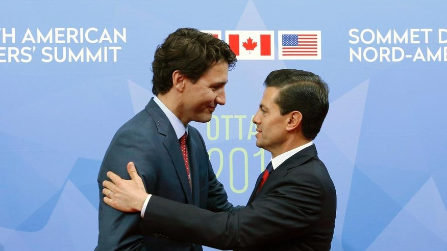 FILE - In this June 29, 2016 file photo, Canada Prime Minister Justin Trudeau welcomes Mexican President Enrique Pena Nieto to the North American Leaders' Summit in Ottawa. Canada has seen a surge of visitors from Mexico since December 2016, when it lifted a visa requirement that had been imposed in 2009. (Fred Chartrand/The Canadian Press via AP, File) MANDATORY CREDIT