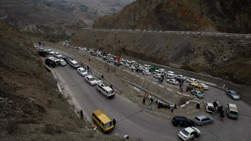 FILE - In March 7, 2017 file photo, vehicles carrying Afghan nationals, travel through Pakistan's famous Khyber Pass en route to neighboring Afghanistan near Torkham border post in Pakistan.The closure of the border between Pakistan and Afghanistan, blamed on deteriorating relations, is more than inconvenient, it is costly. Officials on both sides of the border say in just one month the closure has resulted in hundreds of thousands of dollars in lost trade and tons of perishable goods have rotted in stranded trucks. (AP Photo/Muhammad Sajjad, File)