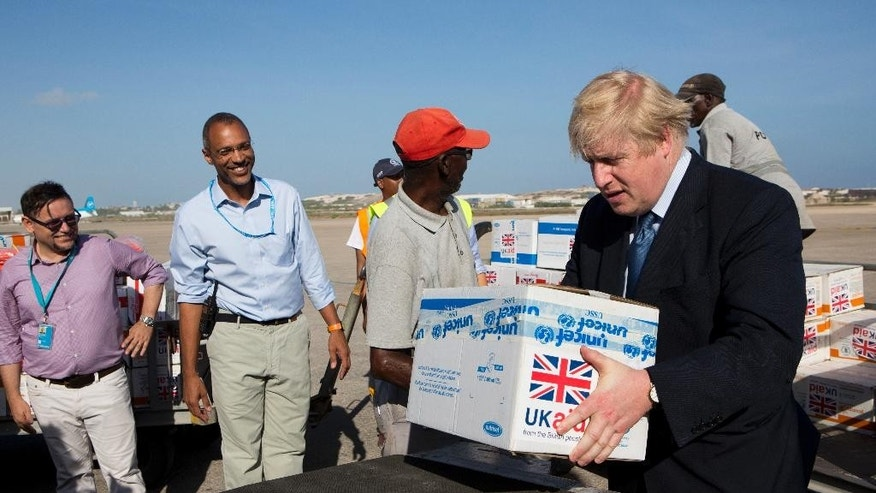 Britain's Foreign Secretary Boris Johnson helps to load food supplies for treating malnourished children affected by the severe drought in Somalia, onto a cargo plane at the airport in Mogadishu, Somalia Wednesday, March 15, 2017. Johnson made a surprise visit to Somalia on Wednesday for talks with the country's new president as a worsening drought threatens millions of people in the Horn of Africa nation. (Karel Prinsloo/UNICEF via AP)