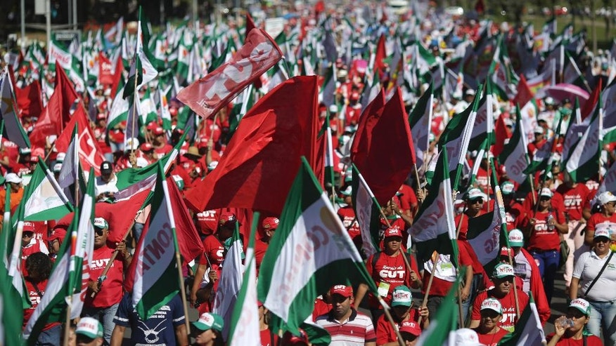 Demonstrators participate in a protest march in Brasilia, Brazil, Wednesday, March 15, 2017. Thousands marched against pension reforms proposed by Brazil's President Michel Temer's government. (AP Photo/Eraldo Peres)