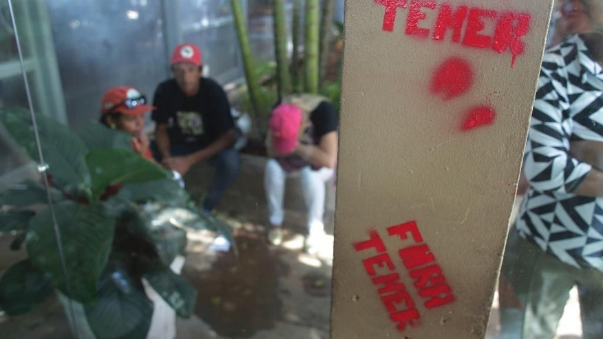 "The words ""Temer Out"" are stenciled in Portuguese on a column of the Economy Ministry headquarters during protest against pension reforms proposed by Brazil's President Michel Temer's government, in Brasilia, Brazil, Wednesday, March 15, 2017. (AP Photo/Eraldo Peres)"
