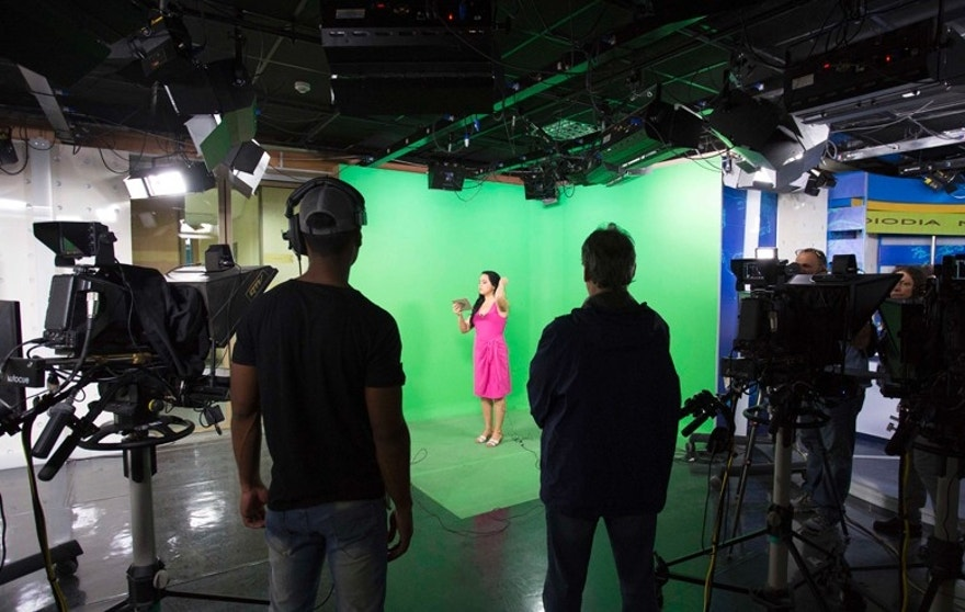 A news presenter reads her card as camera operators stand by during the filming of a news program at the Cuban State Television and Radio headquarters in Havana, Cuba, Tuesday, March 14, 2017. The Cuban government is trying to reboot its Soviet-era style news programming with a high-definition current affairs channel staffed by young journalists, called the Caribe channel. (AP Photo/Desmond Boylan)