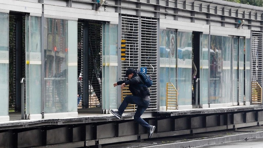 "A man jumps to the boarding area of a public bus station, to evade the fare in Bogota, Colombia, Monday, March, 13, 2017. According to a new civil code applied throughout Colombia filled with stiff penalties, turnstile jumpers on public buses are being sent to enroll in a ""coexistence course."" (AP Photo/Fernando Vergara)"