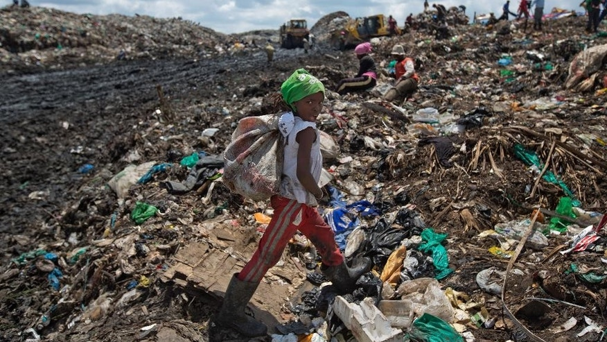 FILE - In this Thursday, Nov. 12, 2015 file photo, Joyce Njeri, 8, walks with a torn sack carrying the plastic she has scavenged, at the garbage dump in the Dandora slum of Nairobi, Kenya. Kenya's government has announced it will become the latest African country to ban the manufacture and import of all plastic bags used for commercial and household packaging, which have littered the streets of the capital Nairobi and created towering piles at dump sites. (AP Photo/Ben Curtis, File)