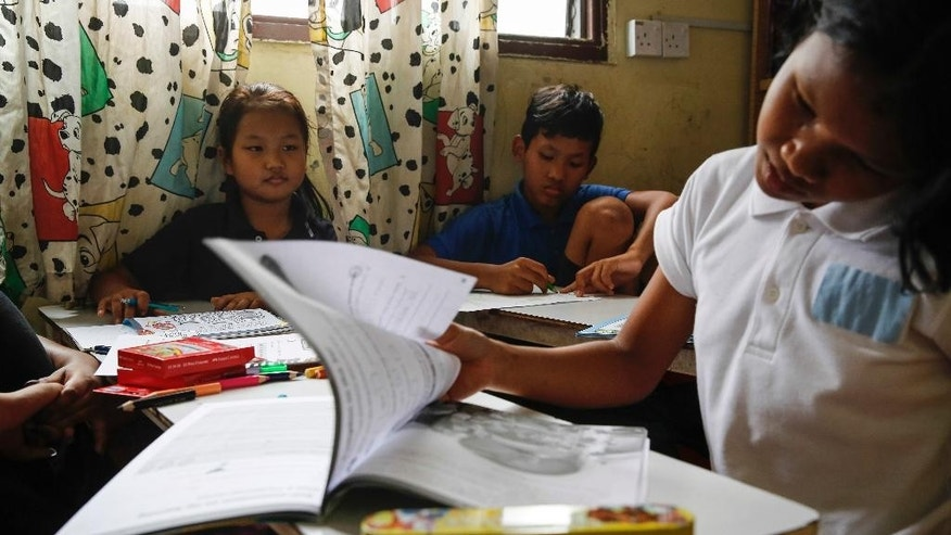 In this March 11, 2017, photo, Christian Burmese refugees study during an English lesson in Kuala Lumpur, Malaysia. An Associated Press analysis suggests that the people hurt most by President Donald Trump's planned deep cuts in refugee visas are from not any of the six Muslim countries listed in his travel ban, but Myanmar. (AP Photo/Joshua Paul)