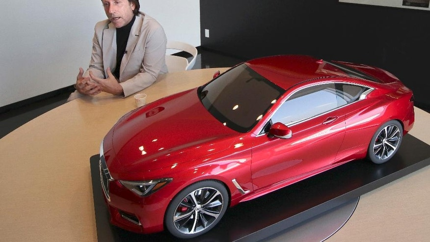In this Feb. 27, 2017 photo, Nissan's design chief Alfonso Albaisa speaks with a model of Infiniti Q60 during an interview at the Nissan Technical Center in Atsugi, near Tokyo. Albaisa draws upon the cultures of Japan, America and Cuba in concocting car designs with a flair that once was lacking at Japanese automakers, critics say, but is becoming evident as they globalize. (AP Photo/Shizuo Kambayashi)
