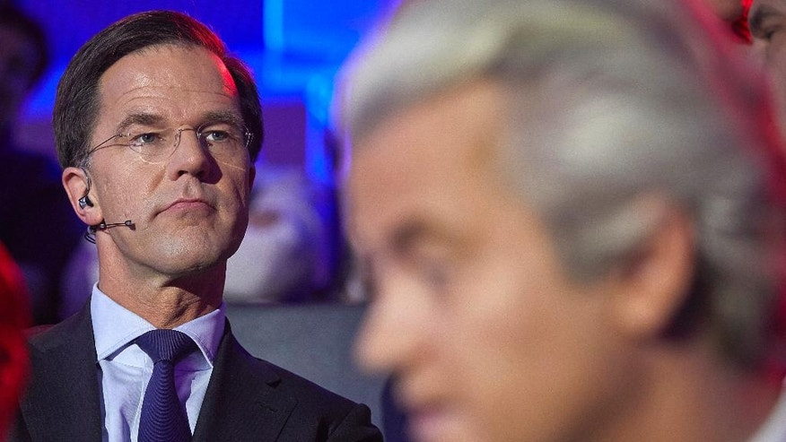 Dutch Prime Minister Mark Rutte, left, and PVV party leader Geert Wilders, right, wait to take their turn in the closing debate at parliament in The Hague, Netherlands, Tuesday, March 14, 2017. Amid unprecedented international attention, the Dutch go to the polls Wednesday in a parliamentary election that is seen as a bellwether for the future of populism in a year of crucial votes in Europe. (Phil Nijhuis HH POOL via AP)