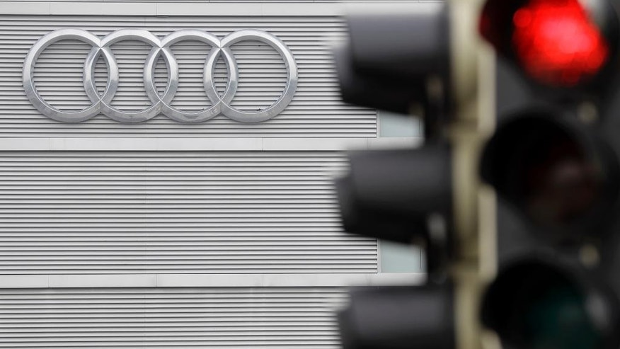 The logo of German car producer Audi is photographed behind a red light prior to the annual press conference in Ingolstadt, Germany, Wednesday, March 15, 2017. German media report that authorities are searching offices of Audi in connection with an investigation into the luxury automaker's parent company Volkswagen's cheating on diesel emissions tests. (AP Photo/Matthias Schrader)