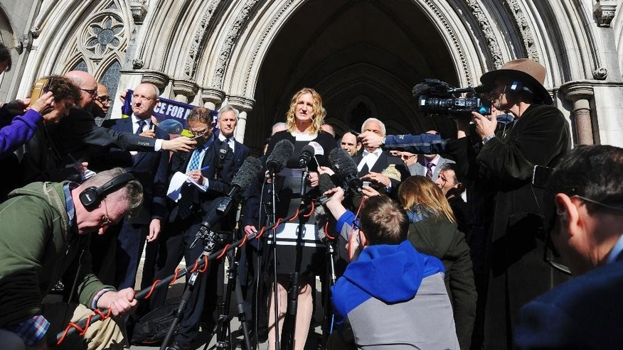 Claire Blackman, centre, the wife of convicted British Royal marine Alexander Blackman, speaks to the media outside the High Court in London Wednesday March 15, 2017.  Blackman who shot an injured Taliban fighter in Afghanistan has had his murder conviction downgraded Wednesday. The murder conviction of 42-year-old Sgt. Alexander Blackman has been quashed and replaced by a manslaughter conviction.  (Lauren Hurley/PA via AP)