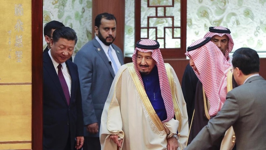 Saudi King Salman, center, and Chinese President Xi Jinping, left, arrive for a signing ceremony at the Great Hall of the People in Beijing, China, Thursday, March 16, 2017. Salman began a visit to Beijing Thursday that highlights growing ties underpinned by China's thirst for Saudi oil and the kingdom's status as a key link in Beijing's bid to connect China to Europe through infrastructure development. (Lintao Zhang/Pool Photo via AP)