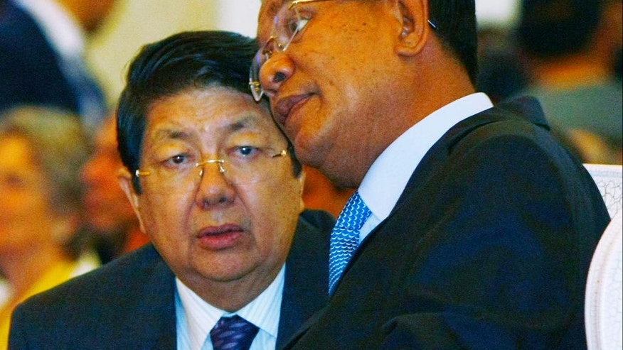 In this June 16, 2013, photo, Cambodian Deputy Prime Minister Sok An, left, talks with Prime Minister Hun Sen, right, in Phnom Penh, Cambodia. A government statement said Wednesday, March 15, 2017, that Sok An, who was one of Prime Minister Hun Sen's closest political and personal allies, has died at age 66. (AP Photo/Heng Sinith)