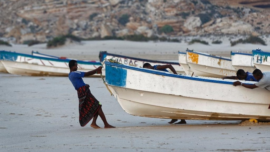 In this photo taken Tuesday, March 7, 2017, fishermen pull their boats into the Indian Ocean shortly after dawn in the former pirate village of Eyl, in Somalia's semiautonomous northeastern state of Puntland. The recent hijacking of an oil tanker has surprised the international shipping community, as many Somali pirates had quit and turned to fishing as anti-piracy patrols increased, but local officials have warned that rampant fishing by foreign trawlers is destroying the fishermen's livelihoods and stoking fears of a return of piracy as a way to make money. (AP Photo/Ben Curtis)