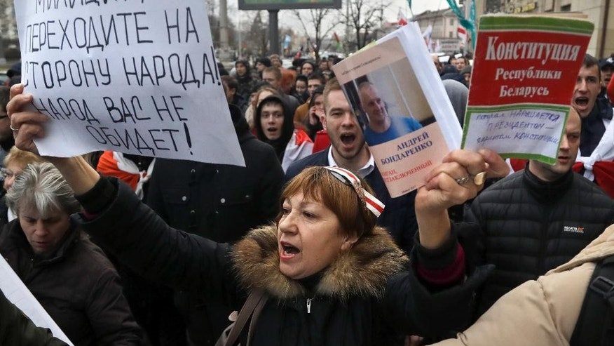 "People shout slogans at a rally in Minsk, Belarus, Wednesday, March 15, 2017. Wednesday's march in the capital Minsk and smaller rallies at several other Belarusian cities were the latest in a series of demonstrations against the law that obliges citizens to pay the equivalent of $250 if they work less than half the year and do not register with state labor exchanges. Banner on the left reads ""Police, go over to the side of the people. The people will not offend you"" and the red banner on the right ""The Constitution of the Republic of Belarus - which is violated by the president, the guarantor of the constitution"". (AP Photo/Sergei Grits)"